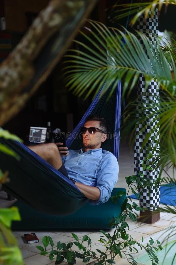 Przystojny mężczyzny lying on the beach na hammok z smartphone Młodego modnisia texting wiadomość na jego telefonie komórko zdjęcia stock