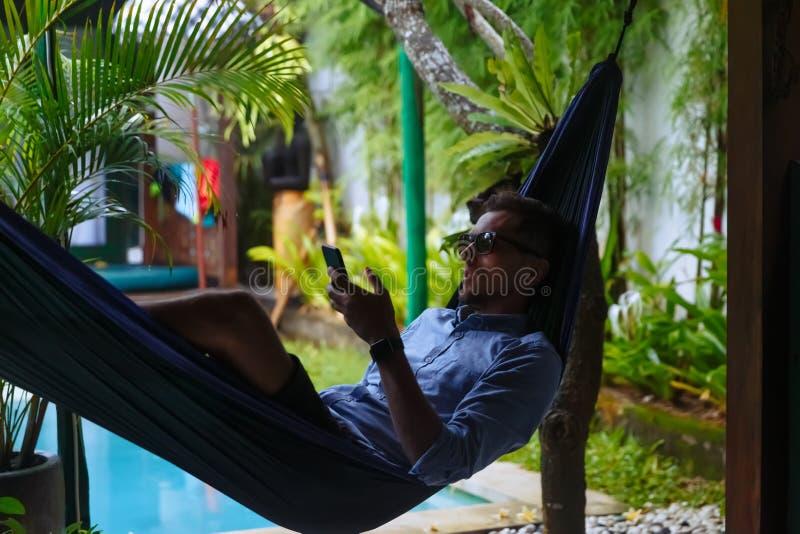 Przystojny mężczyzny lying on the beach na hammok z smartphone Młodego modnisia texting wiadomość na jego telefonie komórko obraz royalty free