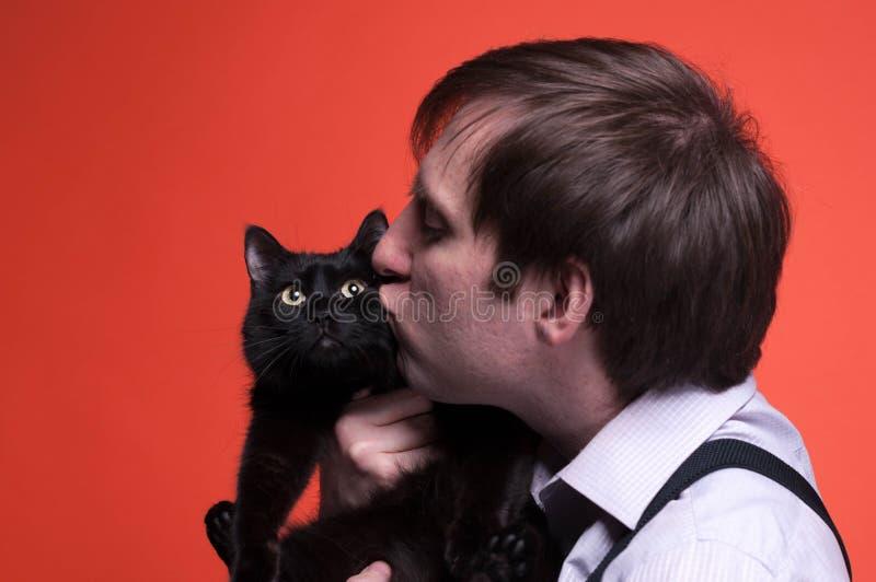 Przystojny mężczyzny mienie, całowanie na kagana czarnym kocie i zdjęcie stock