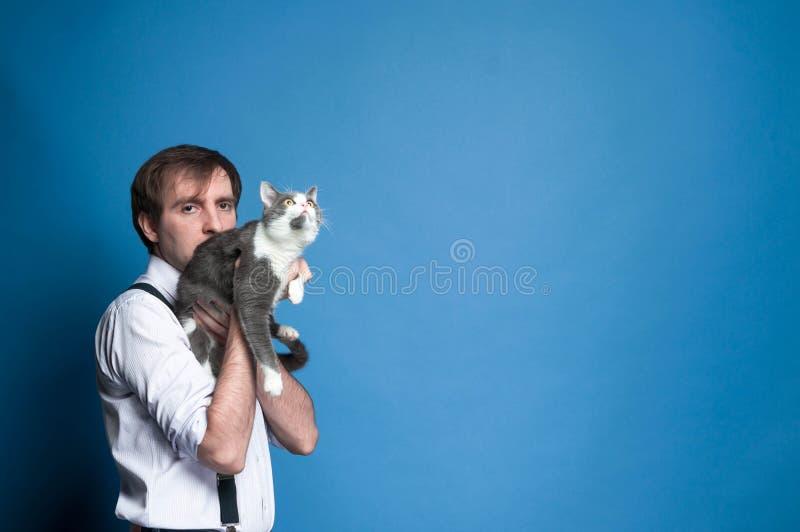 Przystojny mężczyzny mienie i przytulenie popielaty kot patrzeje daleko od na błękitnym tle zdjęcia royalty free