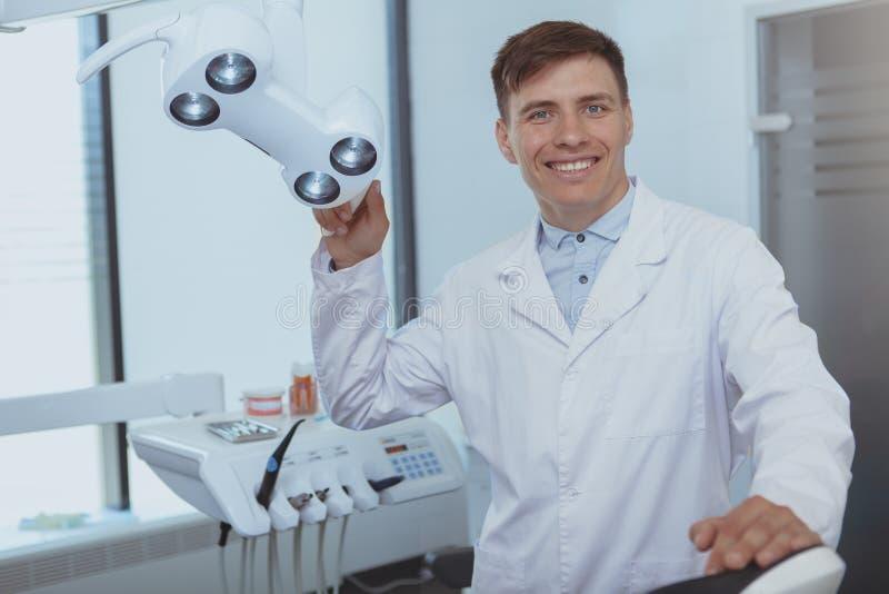 Przystojny męski dentysta pracuje przy jego kliniką zdjęcie stock