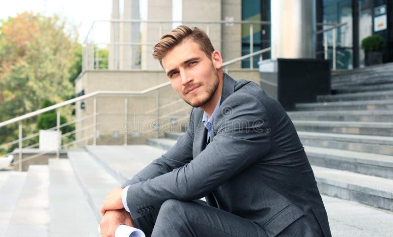 Przystojny męski dyrektora wykonawczego obsiadanie na schodkach na zewnątrz budynku zdjęcia stock
