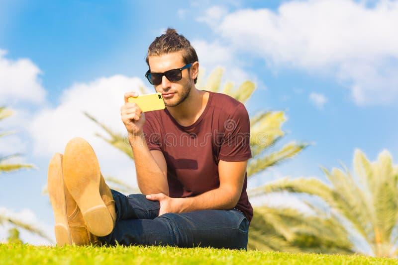 Przystojny męski obsiadanie w parku używać telefon komórkowego obraz royalty free