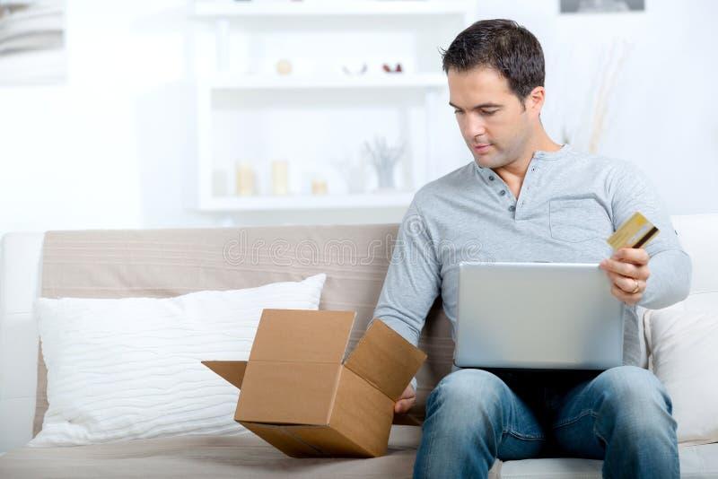 Przystojny męski online zakupy z pakuneczkiem otrzymywającym i kartą kredytową fotografia stock