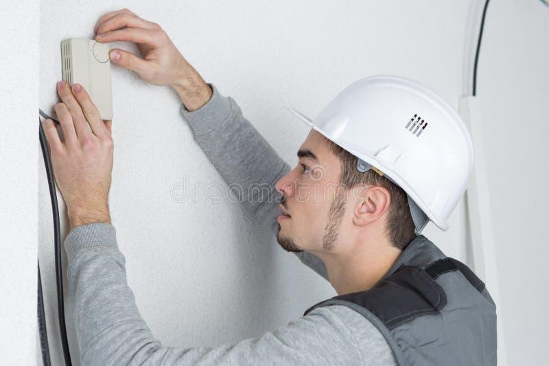 Przystojny młodego człowieka elektryk instaluje powietrze uwarunkowywać w klienta domu fotografia royalty free