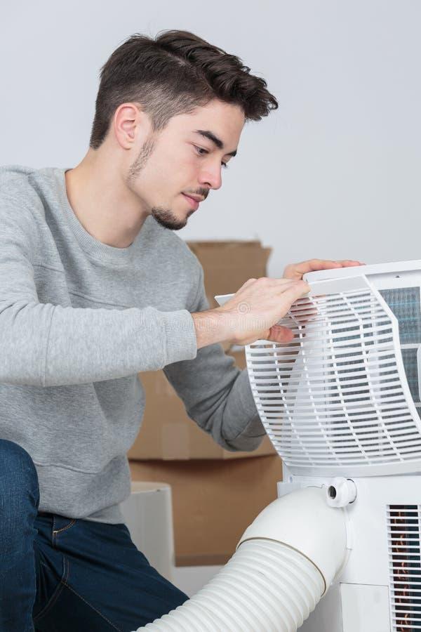Przystojny młodego człowieka elektryk instaluje powietrze uwarunkowywać w klienta domu zdjęcia royalty free