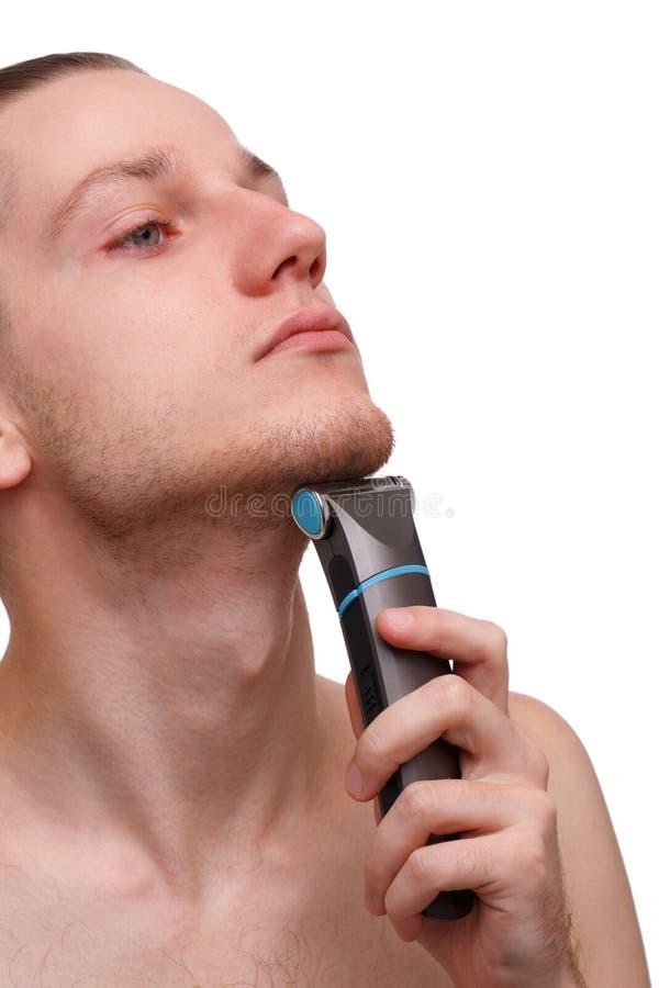 Przystojny młodego człowieka golenie z elektryczną żyletką odizolowywającą nad białym tłem i patrzeć kamerę fotografia stock
