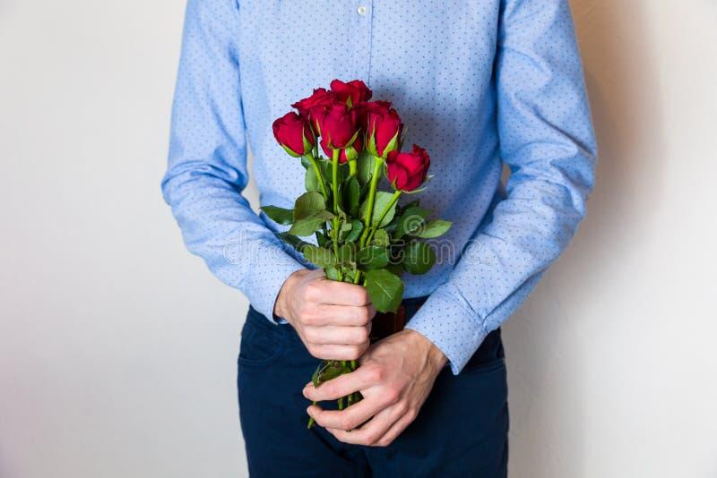Przystojny młodego człowieka mienia czerwieni róży bukiet, romantyczna walentynka dnia niespodzianka, miłość, kwitnie fotografia royalty free