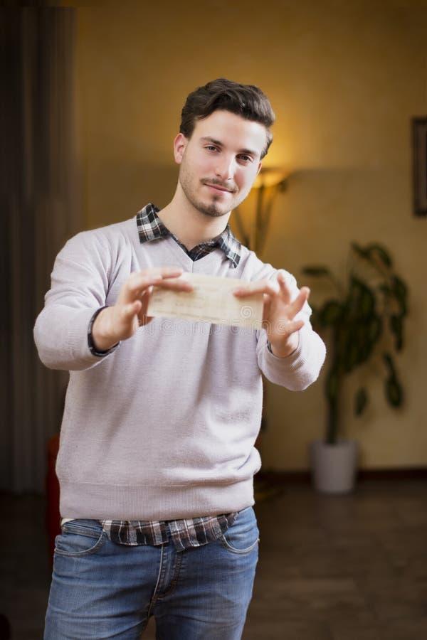 Przystojny młodego człowieka mienie sprawdza wewnątrz jego ręki zdjęcia royalty free