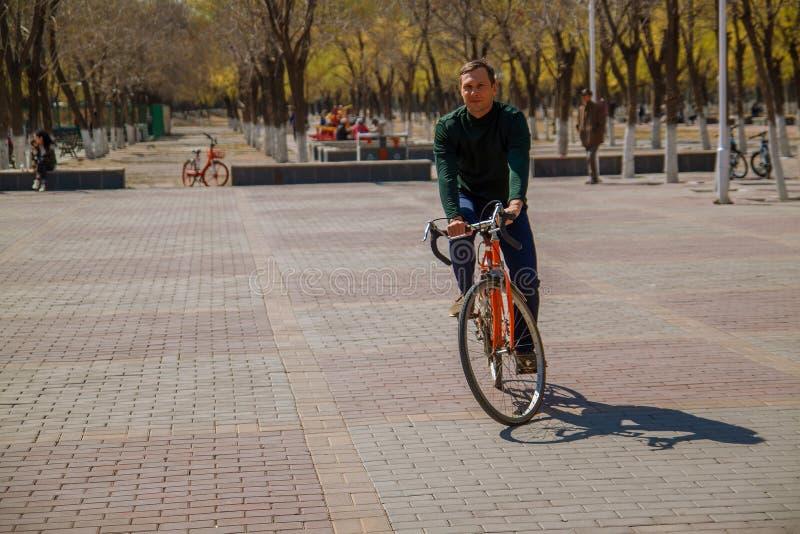 Przystojny młodego człowieka obsiadanie na rowerze i smilling w mieście zdjęcie stock