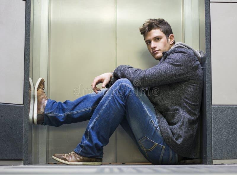 Przystojny młodego człowieka obsiadanie przed wind drzwiami obrazy stock