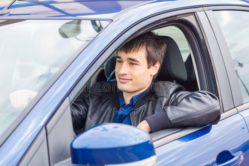 Przystojny młodego człowieka obsiadanie w jego samochodzie obraz stock