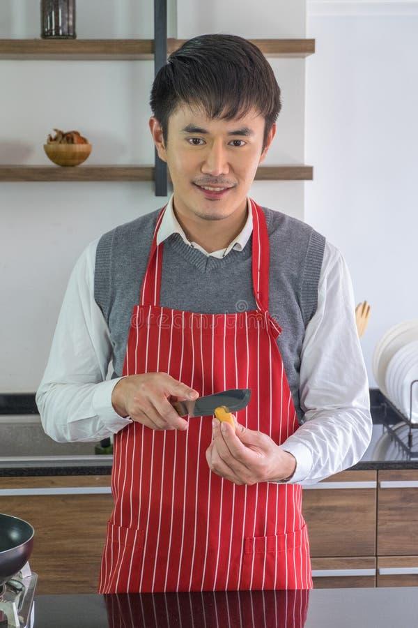 Przystojny, młodego człowieka Uśmiechnięty szczęście przygotowywać jedzenie w kuchni fotografia royalty free