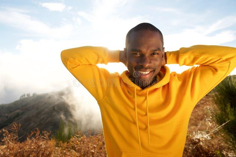 Przystojny młody amerykanin afrykańskiego pochodzenia mężczyzna ono uśmiecha się z rękami za głową outdoors fotografia royalty free
