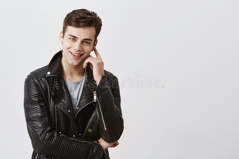 Przystojny młody atrakcyjny mężczyzna patrzeje kamerę z zadowolonym i rozważnym wyrażeniem w czarnej skórzanej kurtce, ono uśmiec obrazy royalty free