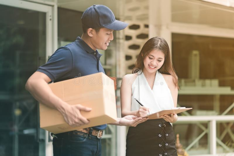 Przystojny młody azjatykci doręczeniowy mężczyzna uśmiecha się karton i trzyma obrazy stock