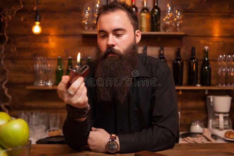 Przystojny młody barman bawić się z jego na zamówienie zapalniczką fotografia royalty free