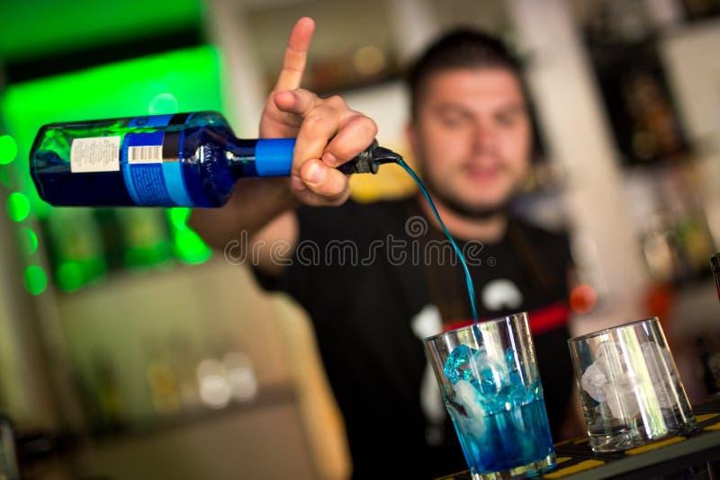 Przystojny młody barman miesza koktajl w barze obrazy stock