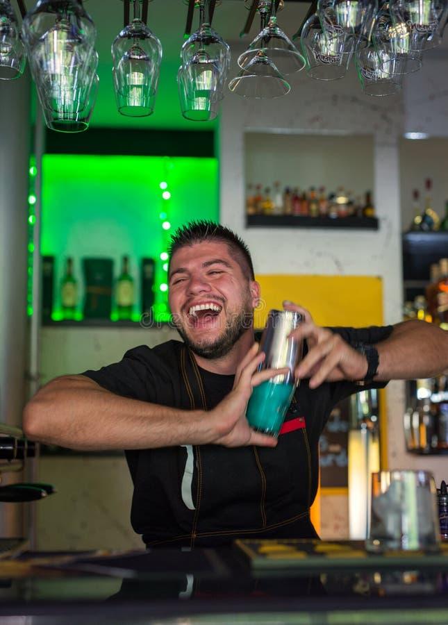 Przystojny młody barman miesza koktajl w barze obraz royalty free
