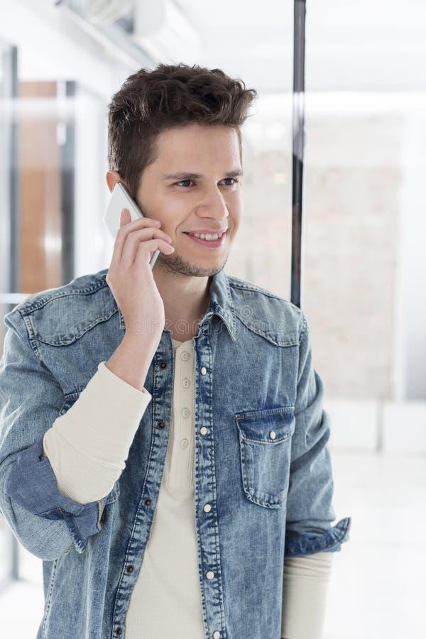 Przystojny młody biznesmen opowiada na smartphone przy biurem obraz stock
