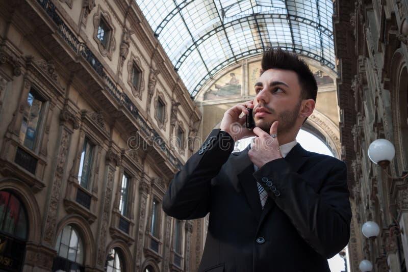 Przystojny młody biznesmen opowiada na telefonie obraz royalty free