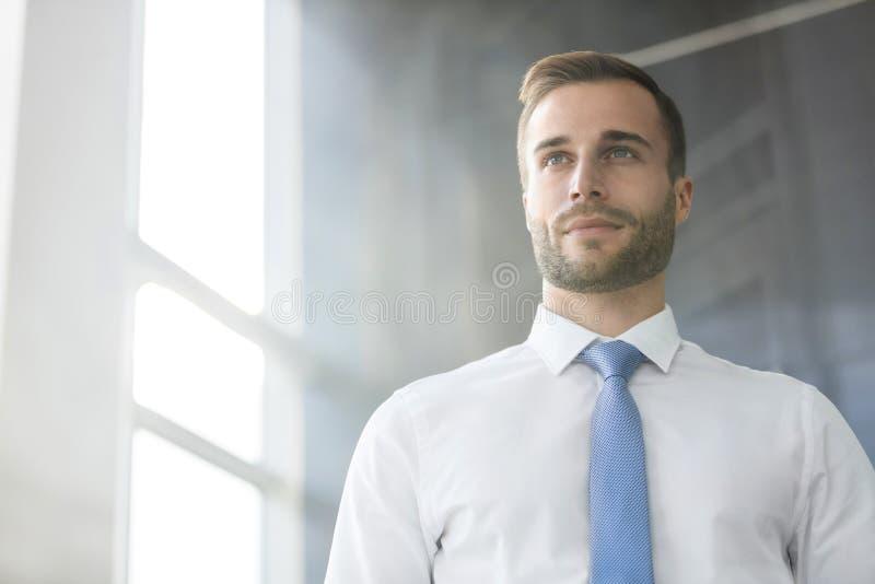 Przystojny młody biznesmen patrzeje oddalony podczas gdy stojący w nowym biurze fotografia royalty free