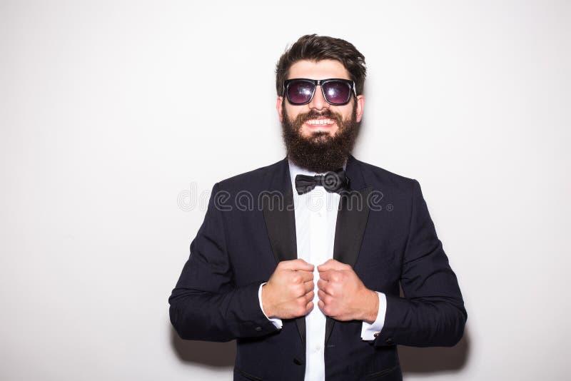 Przystojny młody biznesmen przystosowywa jego kurtkę i patrzeje kamerę podczas gdy stojący fotografia royalty free
