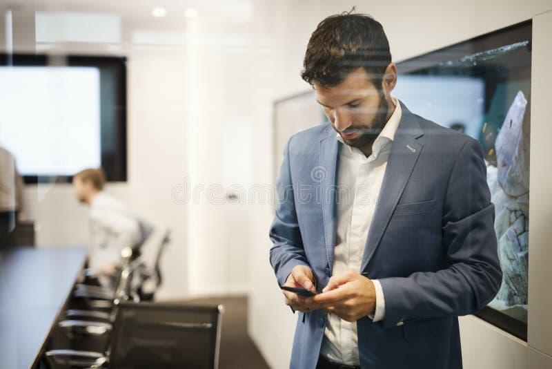Przystojny młody biznesmen w błękitnym kostiumu mienia telefonie komórkowym obrazy stock
