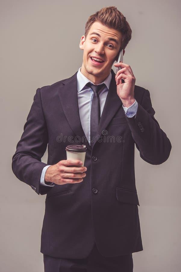 Przystojny młody biznesmen z gadżetem obrazy royalty free