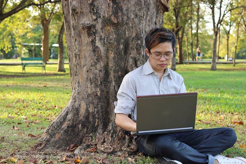 Przystojny młody biznesowy mężczyzna opiera drzewa i używa laptop z jego pracą przy lato parkiem zdjęcie stock