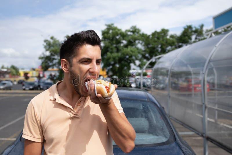 Przystojny młody brunetka mężczyzny łasowania hot dog obraz stock