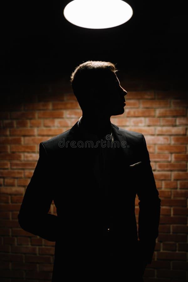 Przystojny młody brunetka model, jest ubranym w czarny i biały kostiumu, fotografia royalty free