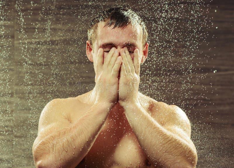 Przystojny młody człowiek bierze prysznic fotografia stock