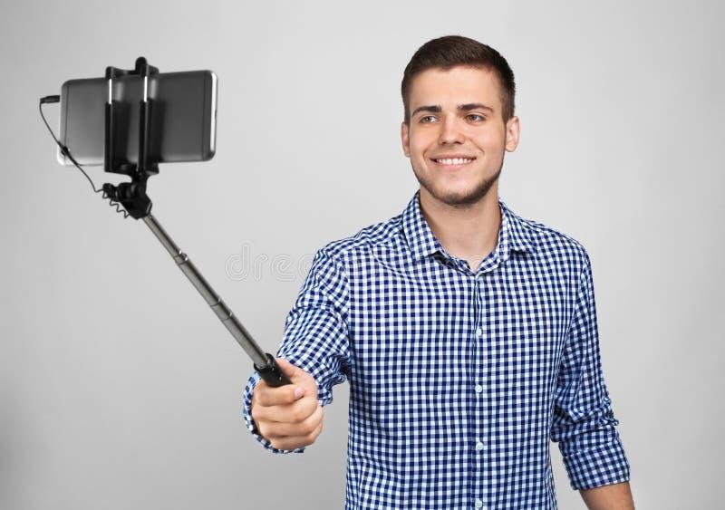 Przystojny młody człowiek bierze selfie na lekkim tle fotografia royalty free