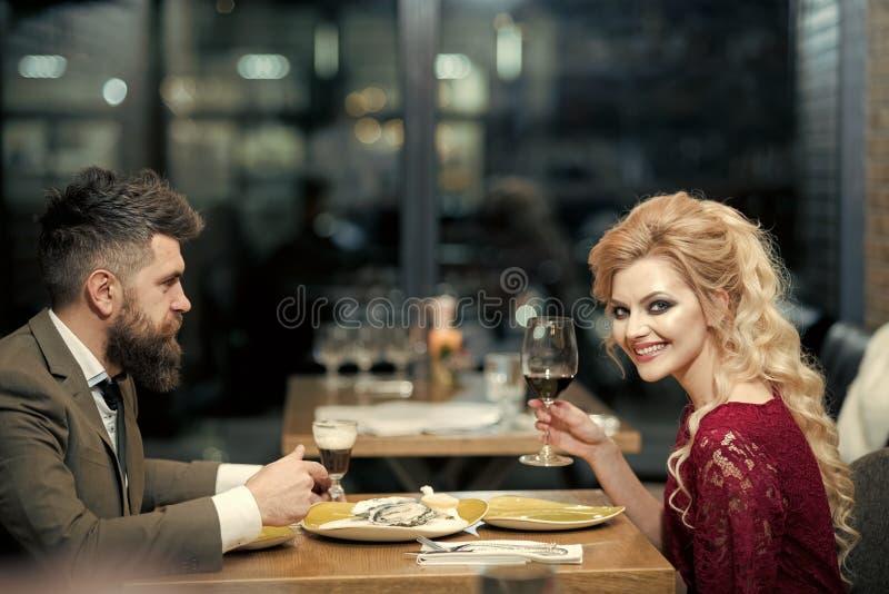 Przystojny młody człowiek i atrakcyjna młoda kobieta wydajemy czas wpólnie Romantyczna para w kawiarni pije wino i obrazy royalty free