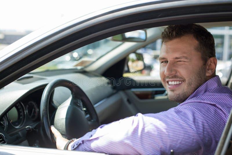 Przystojny młody człowiek jedzie jego samochód fotografia stock