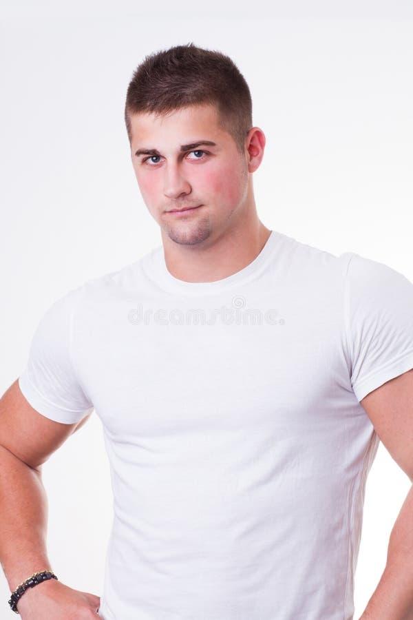 Przystojny młody człowiek jest ubranym białą koszulkę obrazy stock