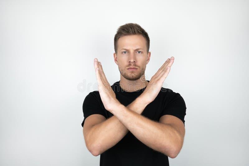 Przystojny młody człowiek jest ubranym czarną koszulkę trzyma jego ręki krzyżował pokazywać negatywny wyrażenie odizolowywającego zdjęcie stock