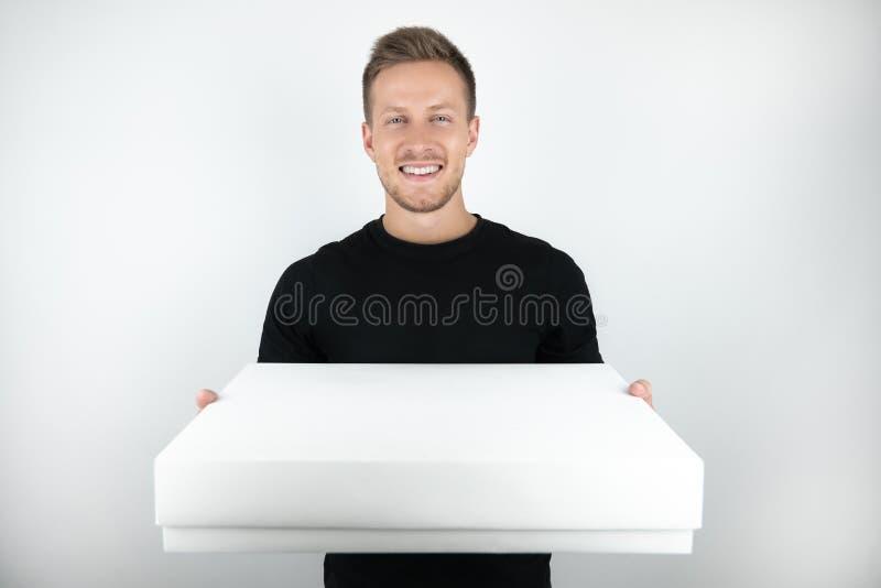 Przystojny młody człowiek jest ubranym czarnego koszulki mienia pakuneczek w papierowym pudełku dla dostawy na odosobnionym biały zdjęcia stock