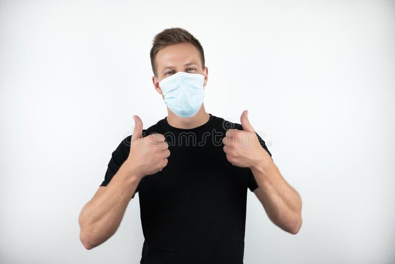 Przystojny młody człowiek jest ubranym medyczną maskę pokazuje ok znaka z oba rękami na odosobnionym białym tle w czarnej koszulc obraz stock