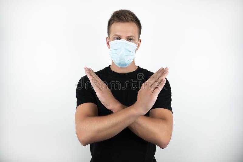 Przystojny młody człowiek jest ubranym medyczną maskę trzyma jego ręki w czarnej koszulce krzyżował na odosobnionym białym tle zdjęcie stock