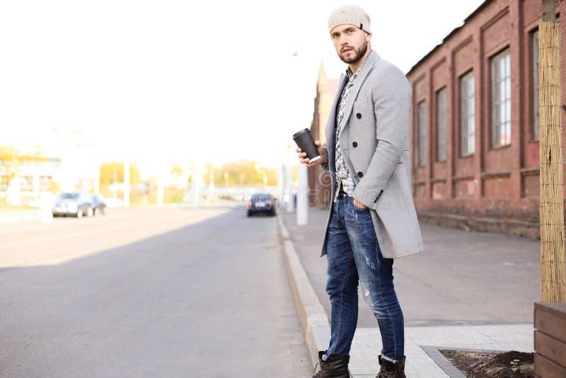 Przystojny młody człowiek krzyżuje ulicę w popielatym żakiecie i kapeluszu z filiżanka kawy fotografia royalty free