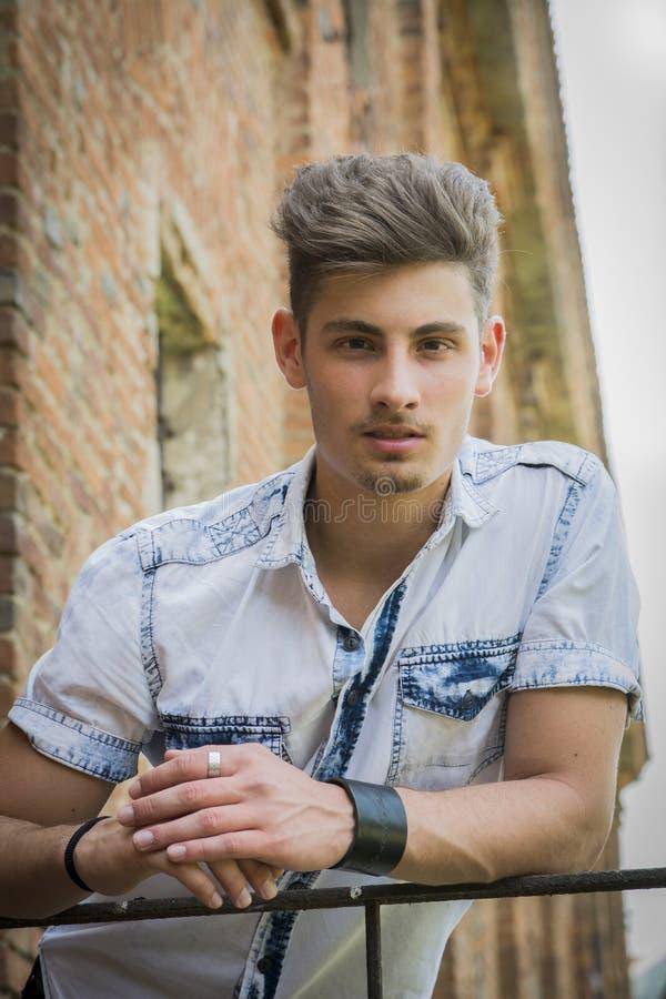 Przystojny młody człowiek outdoors opiera na poręczu obrazy stock