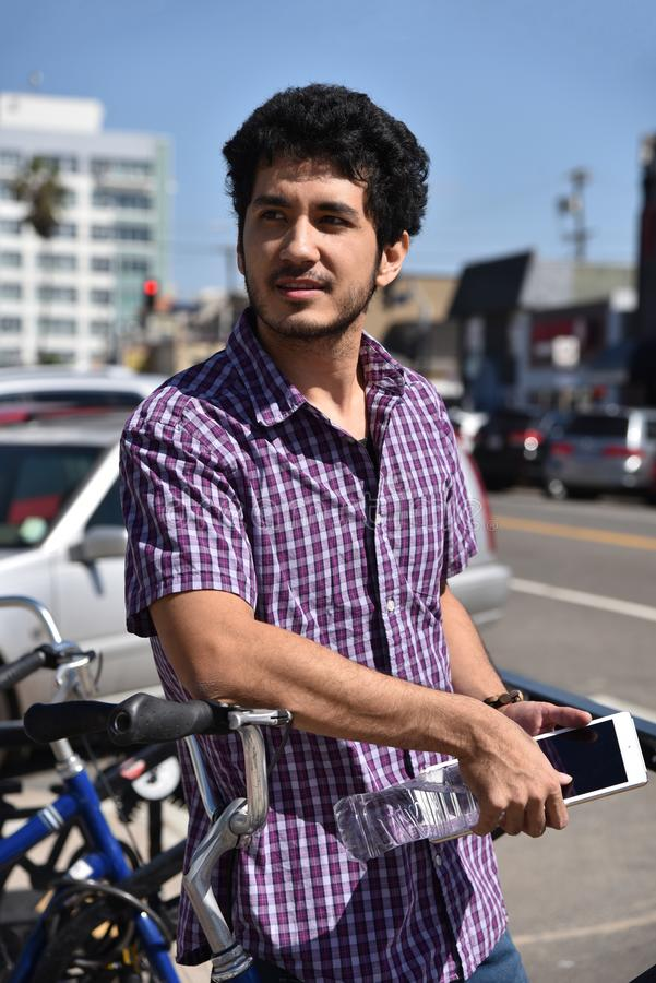 Przystojny młody człowiek outdoors używa technologię fotografia stock