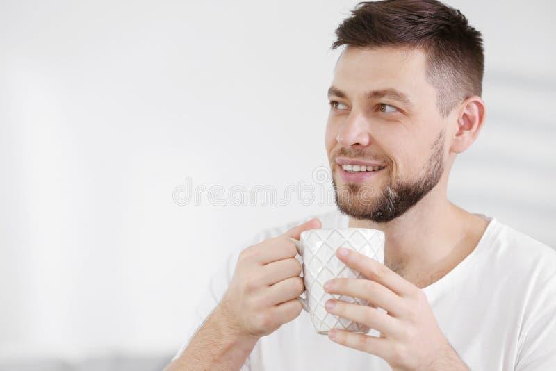 Przystojny młody człowiek pije kawę w domu obrazy royalty free