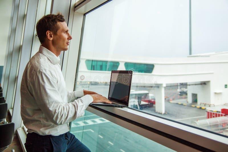 Przystojny młody człowiek pracuje z laptopem w lotnisku gdy czekać na jego samolot zdjęcia stock