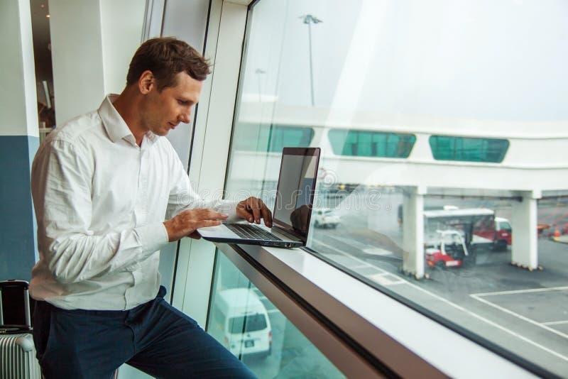 Przystojny młody człowiek pracuje z laptopem w lotnisku gdy czekać na jego samolot zdjęcia royalty free