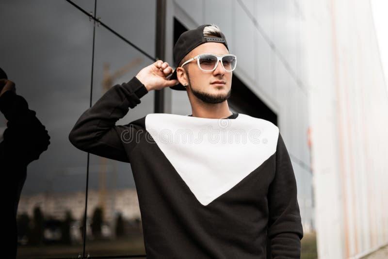 Przystojny młody człowiek prostuje czarną baseball nakrętkę Atrakcyjny modnisia facet w roczników okularach przeciwsłonecznych w  zdjęcie stock