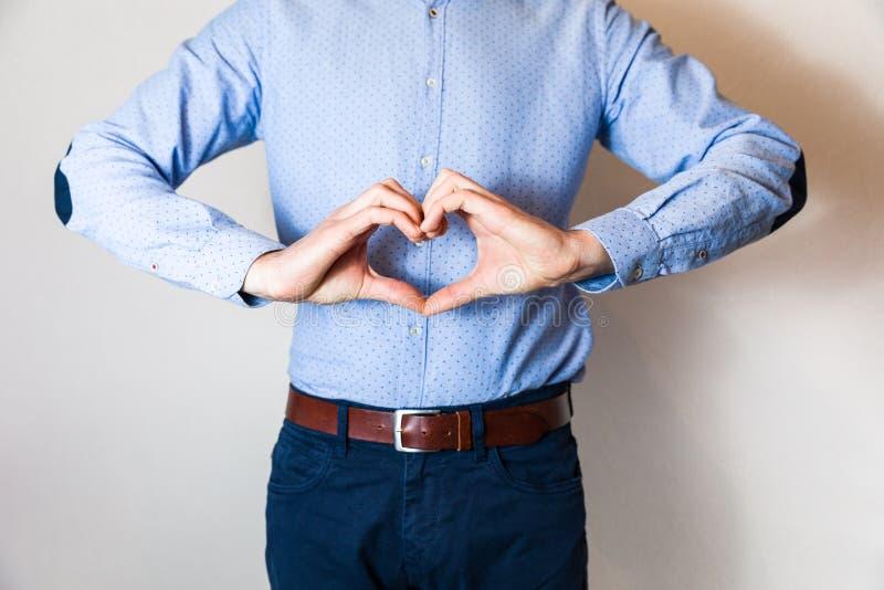 Przystojny młody człowiek robi kierowemu kształtowi z ręka palcami, miłość, związek, datuje zdjęcie stock