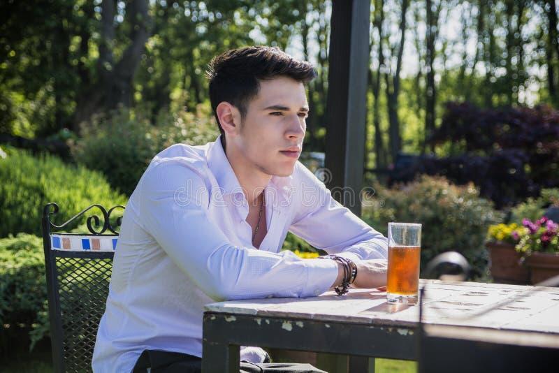 Przystojny młody człowiek siedzi samotnie przy stołowym outside zdjęcia royalty free